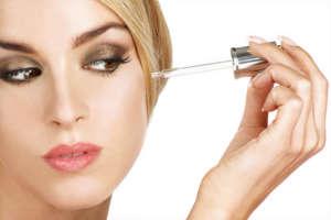 beautiful model applying a skin serum treatment on white